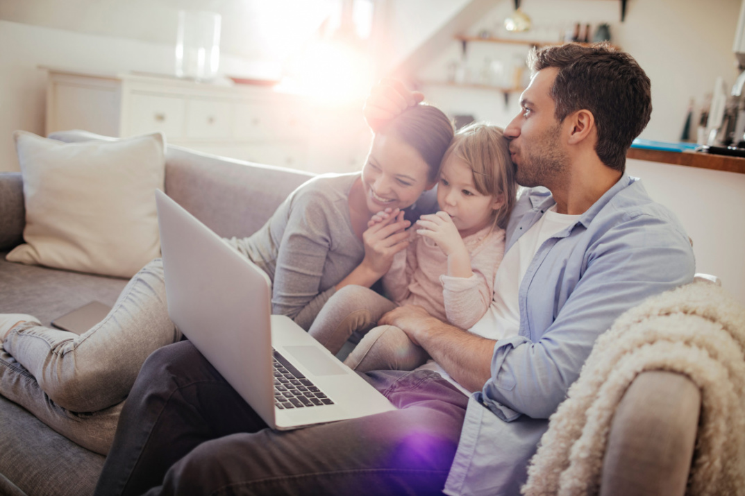 Family sitting together in front of laptop