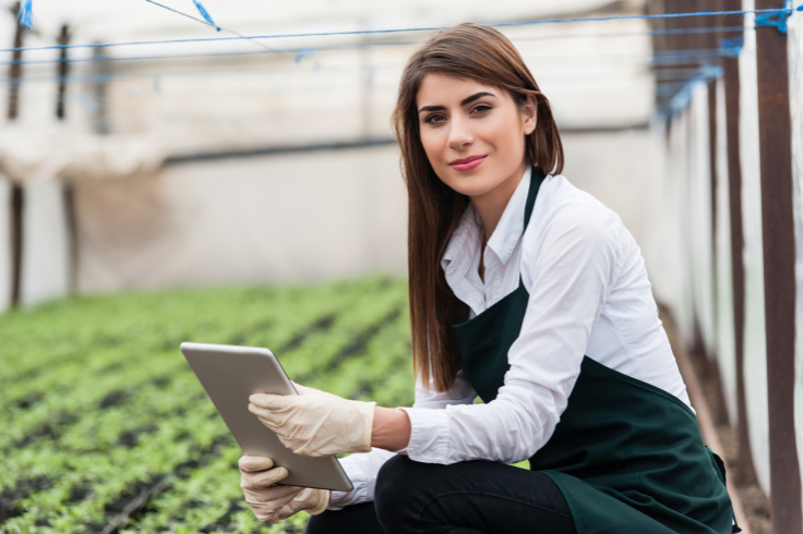 Young woman in workwear and with a tablet in her hand kneels in front of a field with sprouts